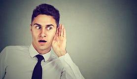 Portret przystojny biznesowy mężczyzna skrycie słucha na prywatnej rozmowie zdjęcie stock