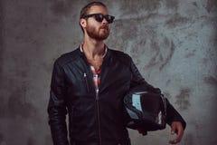 Portret przystojny elegancki rudzielec rowerzysta w czarnej skórzanej kurtce i okularach przeciwsłonecznych, chwyta motocyklu heł obraz royalty free