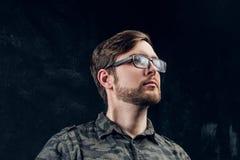 Portret przystojny facet w elegancki militarny koszulowy patrzeć z ukosa Pracowniana fotografia z ciemnym tłem zdjęcie stock