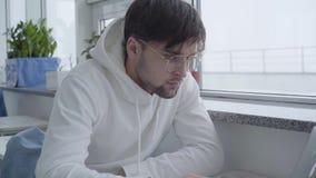 Portret przystojny faceta obsiadanie w cukiernianym lub w, czekać na jego rozkaz uważnie przy komputerem centrum i działaniu zbiory wideo