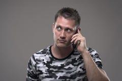 Portret przystojny młody dorosły mężczyzna opowiada na telefonie i patrzeje ciekawie w górę kopii przestrzeni przy zdjęcia royalty free