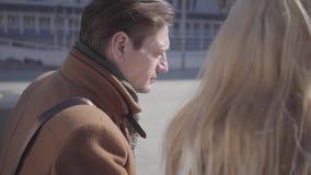 Portret przystojny mężczyzna i ładna blond kobieta w ciepłym kurtki obsiadaniu przy miasta uliczny opowiadać Pary gawędzenie zdjęcie wideo