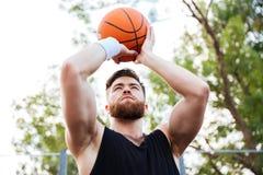 Portret przystojny mężczyzna w sportach jest ubranym bawić się koszykówkę fotografia stock