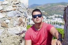 Portret przystojny mężczyzna z czarnymi okularami przeciwsłonecznymi na dennym kurortu tle fotografia royalty free