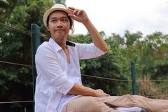 Portret przystojny młodego człowieka relaksować siedzi na bridżowej podłoga przy parkiem outdoors zdjęcie stock