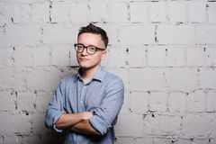 Portret przystojny młody człowiek patrzeje kamerę ono uśmiecha się w cajgach odzieżowych i eyeglasses, stoi przeciw szarej cegle Zdjęcia Royalty Free