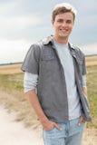 Portret przystojny młody człowiek stoi na polu z rękami w kieszeniach Zdjęcia Stock