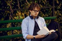 Portret przystojny młody człowiek w eyeglasses i hełmofonach, czyta książkowy outside, odosobniony na miastowym parkowym tle zdjęcie stock