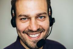 Portret przystojny młody męski operator patrzeje kamerę i ono uśmiecha się w słuchawki podczas gdy stojący przeciw bielowi Obrazy Royalty Free