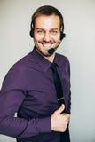Portret przystojny młody męski operator patrzeje kamerę i ono uśmiecha się w słuchawki podczas gdy stojący przeciw bielowi Zdjęcie Royalty Free