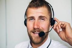 Portret przystojny młody męski operator patrzeje kamerę i ono uśmiecha się w słuchawki podczas gdy stojący przeciw bielowi Obraz Royalty Free