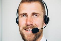 Portret przystojny młody męski operator patrzeje kamerę i ono uśmiecha się w słuchawki podczas gdy stojący przeciw bielowi Zdjęcia Royalty Free