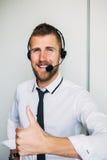 Portret przystojny młody męski operator patrzeje kamerę i ono uśmiecha się w słuchawki podczas gdy stojący przeciw bielowi Fotografia Stock