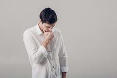Portret przystojny młody zadumany mężczyzna w białej koszula na szarych półdupkach Obrazy Royalty Free