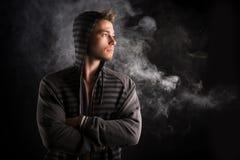 Portret przystojny twardy młody człowiek w ciemnym hoodie obraz royalty free