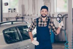 Portret przystojny, uśmiechnięty auto mechanik w błękitnym kombinezonie, ch zdjęcie royalty free