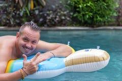 Portret przystojny uśmiechnięty mężczyzna na nadmuchiwanej materac w pływackim basenie przy słonecznym dniem bali Obraz Royalty Free