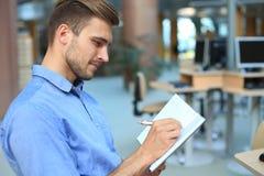 Portret przystojny uśmiechnięty mężczyzna w przypadkowej koszula bierze notatki przy miejscem pracy zdjęcia stock