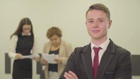 Portret przystojny ufny młody człowiek ono uśmiecha się pokazywać dużego palec podczas gdy jego żeńscy koledzy pracuje z papieram zbiory