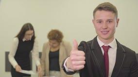 Portret przystojny ufny młody człowiek uśmiecha się patrzeć in camera podczas gdy jego żeńscy koledzy pracuje z papierami wewnątr zdjęcie wideo