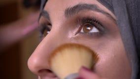 Portret ręki robi oko makijażowi z małymi i dużymi muśnięciami dla pięknej muzułmańskiej damy w hijab dalej bricken ścianę zbiory