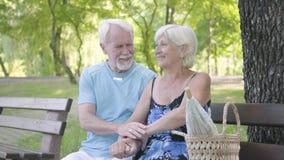 Portret radości pary dojrzały obsiadanie na ławce podziwia naturę Starszy mężczyzna i kobieta relaksuje wpólnie leisure zbiory wideo