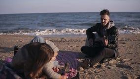 Portret radosna, uśmiechnięta rodzina, siedzi na szkockiej kraty koc na plaży jako ojciec sztuki matki z i gitarę zdjęcie wideo
