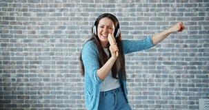 Portret radosny dama śpiew w hairbrush tanu na ściany z cegieł tle zbiory wideo