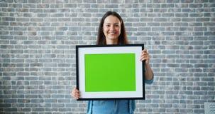 Portret radosny dziewczyny przewożenia zieleni ekranu obrazek na ściany z cegieł tle zbiory wideo