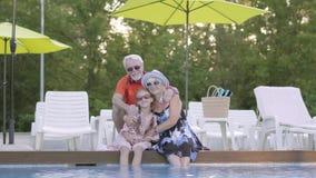 Portret rijp paar die weinig kleindochter op de rand van de pool koesteren Grootmoeder, grootvader en kleinkind stock video