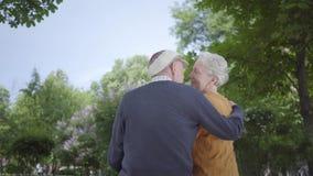 Portret rijp paar in liefdezitting op een bank in het park Volwassen vrouw en oude man samen Tedere verhouding stock videobeelden
