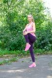 Portret robi rozciąganiu sporty kobieta ćwiczy w parku przed trenować Żeńskiej atlety narządzanie dla jogging obraz royalty free