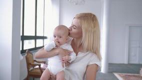 Portret rodzina, śliczna mama trząść jej nowonarodzonej córki w ona przy kamerą ręki i uśmiechy zbiory