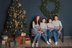 Portret rodzina składająca się z czterech osób w identycznych pulowerach i cajgach na kanapie blisko nowego roku drzewa w żywym p obraz royalty free