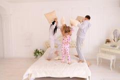 Portret rodzinne walczące poduszki, skacze na łóżku wpólnie wewnątrz Obraz Stock