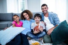 Portret rodzinny dopatrywanie futbolu amerykańskiego dopasowanie na telewizi zdjęcie royalty free