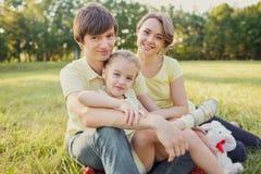 Portret rodzinny obsiadanie w parku na trawie Zdjęcie Royalty Free