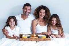 Portret rodzinny obsiadanie z śniadaniową tacą w łóżku Obraz Stock