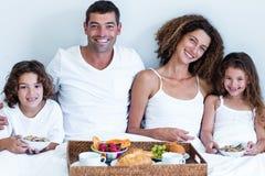 Portret rodzinny obsiadanie z śniadaniową tacą w łóżku Fotografia Royalty Free