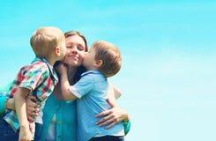 Portret rodziny dwa dzieci synowie całuje mamy, macierzysty ` s dzień, błękitny fotografia stock