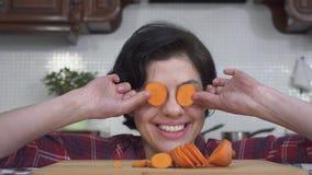 Portret roześmiany i uśmiechnięty dziewczyny kładzenie przed oko pomarańczowymi plasterkami marchewka na tle nowożytny zbiory