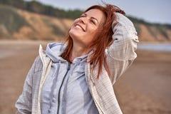 Portret roze?miana w ?rednim wieku kobieta z czerwonym w?osianym odprowadzeniem wzd?u? brzeg rzekiego pogodna ranek wiosna zdjęcie stock