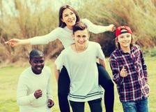 Portret roześmiani przyjaciele biega na polu Fotografia Stock