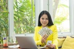 Portret rozochoceni młodzi Azjatyccy kobiety mienia pieniądze banknoty i telefon komórkowy z uśmiechem stawiamy czoło przed kompu zdjęcia royalty free