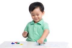 Portret rozochocona azjatykcia chłopiec bawić się z akwarelami Zdjęcie Stock
