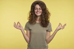 Portret rozochocona brunetki kobieta z kędzierzawym włosy, robi zadowalającemu gestowi, uśmiechom i główkowaniu, coś dobry obrazy stock