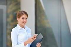 Portret rozochocona młoda kobieta używa smartphone outdoors Obrazy Royalty Free