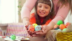 Portret rozochocona małe dziecko dziewczyna bawić się wraz z jego matką z Easter jajkiem na kuchennym tle mienie zbiory