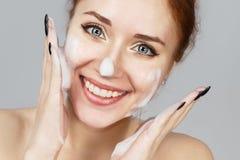 Portret rozochocona roześmiana dziewczyna stosuje pianę dla myć na jej twarzy Urocza kobiety rudzielec z atrakcyjnym pojawieni fotografia stock