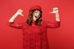 Portret rozochocona ufna młoda kobieta wskazuje kciuki na ona odizolowywałam na jaskrawej czerwieni ścianie w koronki sukni nakrę fotografia royalty free